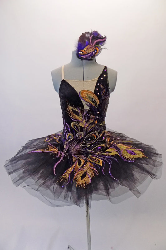 Peacock themed ballet tutu has a black base with beautiful gold & purple embroidered lace designs on the bodice & sheer overlay. The nude straps cross over at the back for good support. The accompanying black pull-on tutu & black briefs create the stunning base. Comes with a large matching hair accessory. Front