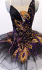 Peacock themed ballet tutu has a black base with beautiful gold & purple embroidered lace designs on the bodice & sheer overlay. The nude straps cross over at the back for good support. The accompanying black pull-on tutu & black briefs create the stunning base. Comes with a large matching hair accessory. Front zoomed