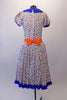 50s housewife themed, pouffe sleeved dress is a white base with colourful squares of blues, yellow & orange. The blue theme is repeated in the collar, sleeve cuffs, buttons & ruffled skirt hem. The orange attached apron compliments the square pattern in the dress with blue crystal accents. Comes with a hair accessory. Back