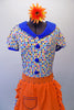 50s housewife themed, pouffe sleeved dress is a white base with colourful squares of blues, yellow & orange. The blue theme is repeated in the collar, sleeve cuffs, buttons & ruffled skirt hem. The orange attached apron compliments the square pattern in the dress with blue crystal accents. Comes with a hair accessory. Front zoomed