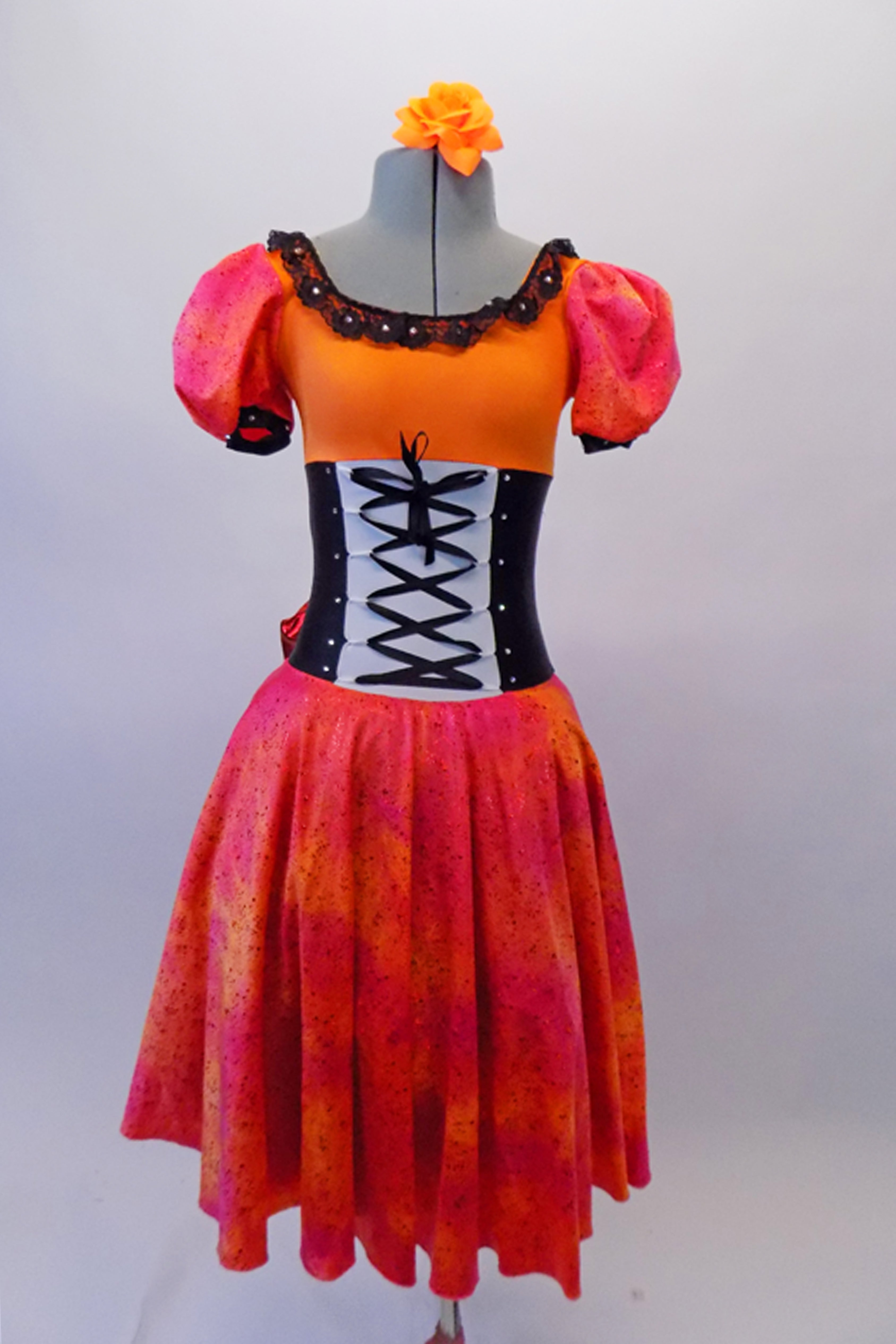 The layers of petticoat and orange bustle with bow, create loads of volume beneath a colourful skirt in shades of red pink & orange. The skirt portion of the dress compliments the orange bodice, ruffled neckline, pouffe sleeves and faux corset laced waistband. Front