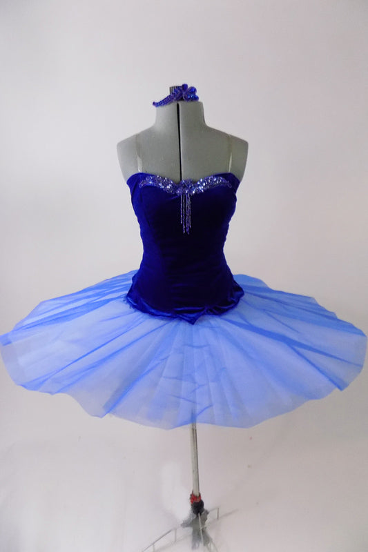Royal blue ballet bodice is princess cut with low back & clear cross-back straps. Front bust area & upper back have beautiful blue beaded appliques. The matching blue sheer overlay has a velvet bask to compliment the bodice & tiny loopholes to attach to a tutu below. Comes with arm pouffes & appliqued hair accessory. Front