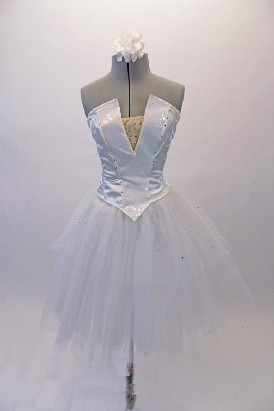 White crystalled ballet bodice has a sequined princess cut center with peaked font & nude sequined insert. There is a zipper closure at back. The white sheer overlay has scattered crystals like droplets of ice that sits over a white romantic pull-on tutu skirt. Comes with white floral hair accessory & removable straps. Front