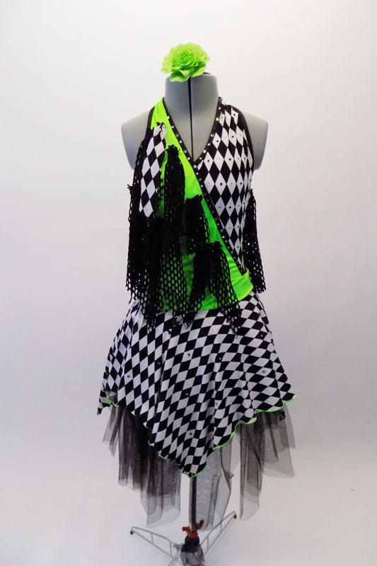 Black & white checkered harlequin themed dress has a lime green cross-over, halter bodice with attached black mesh kerchief accents cascading throughout. Swarovski crystals are scattered within the checkered pattern of the fabric that sits over layers of black tulle. Comes with a green floral hair accessory. Front