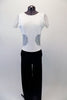 Black and white full unitard has boot-leg cut black velvet pant attached to a white velvet top. The top has sequined mesh inlay along the sleeves and center back that extends to the front at the waist. Crystals line the front of the neckline and sequined waist inlay. Front
