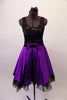 Purple and black tank style dress has a black scoop-neck bodice and black velvet waistband with crystal accents and purple front bow. The attached purple calf length skirt has layers of black tulle for a full petticoat. Comes with floral hair accessory and lace edged purple gauntlets. Front