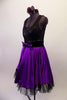 Purple and black tank style dress has a black scoop-neck bodice and black velvet waistband with crystal accents and purple front bow. The attached purple calf length skirt has layers of black tulle for a full petticoat. Comes with floral hair accessory and lace edged purple gauntlets. Side
