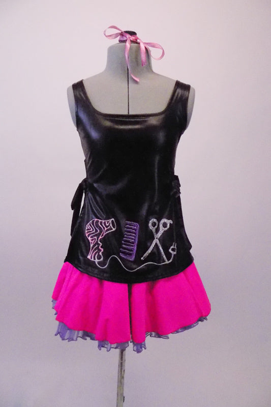 Hairdresser themed costume has black leatherette tunic style top with hand painted scissors, comb and blow drier. The tunic top ties at the sides and sits over top of a bright pink skirt with purple tricot petticoat. Comes with pink hairbow. Front
