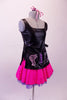 Hairdresser themed costume has black leatherette tunic style top with hand painted scissors, comb and blow drier. The tunic top ties at the sides and sits over top of a bright pink skirt with purple tricot petticoat. Comes with pink hairbow. Right side