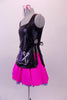 Hairdresser themed costume has black leatherette tunic style top with hand painted scissors, comb and blow drier. The tunic top ties at the sides and sits over top of a bright pink skirt with purple tricot petticoat. Comes with pink hairbow. Left side