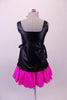 Hairdresser themed costume has black leatherette tunic style top with hand painted scissors, comb and blow drier. The tunic top ties at the sides and sits over top of a bright pink skirt with purple tricot petticoat. Comes with pink hairbow. Back