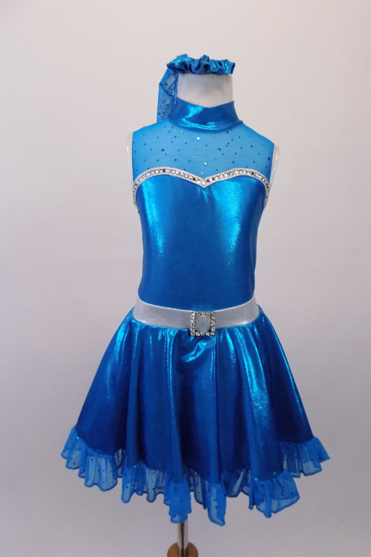 Shimmery turquoise blue crystal lined sweetheart bust dress has silver edging, sheer sparkle upper with a high collar. Back clips at neck with large keyhole opening. The skirt has sheer sparkle ruffle and petticoat with crystal buckle accented silver waistband. Comes with matching hair accessory. Front