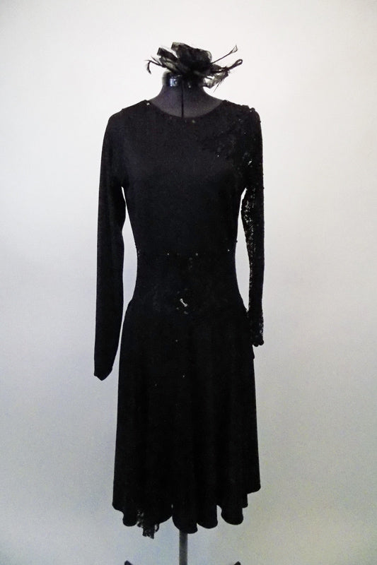 Simply elegant black long-sleeved dress has sheer floral lace left sleeve, shoulder and waistband with a lace cascade from right hip. Comes with flack rose fascinator hair accessory. Front