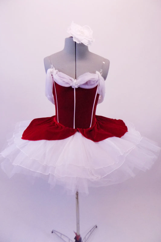 Gorgeous red velvet tutu has a red leotard base with white boning & princess cut. The neckline is draped with white chiffon that joins at the center of the back.  The skirt is comprised of a white tulle pull-on tutu with chiffon & red velvet overlay. Comes with white floral hair accessory & clear straps. Front