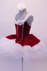 Gorgeous red velvet tutu has a red leotard base with white boning & princess cut. The neckline is draped with white chiffon that joins at the center of the back.  The skirt is comprised of a white tulle pull-on tutu with chiffon & red velvet overlay. Comes with white floral hair accessory & clear straps. Left side