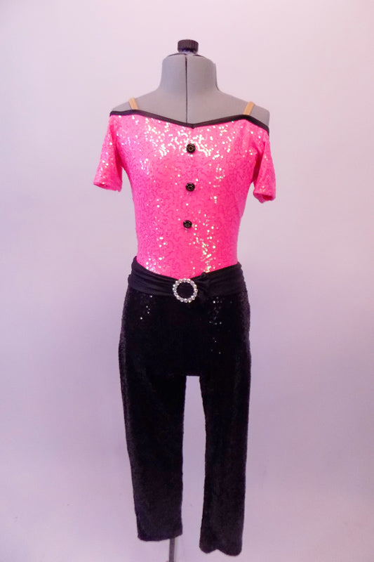 Fully sequined bright pink and black capri-length unitard is an off-shoulder top with black piping, cap sleeves, nude shoulder straps and black button accents. The attached black capri pat is a straight leg with gathered waistband and crystal ring buckle accent. Comes with a hair accessory. Front