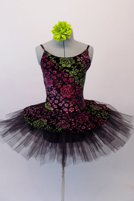 Pretty black pleated six-layer platter tutu has an attached bodice and overlay adorned with a glittery rose floral pattern in shades of pink, green and fuchsia. Comes with a green floral hair accessory. Front