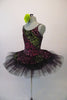 Pretty black pleated six-layer platter tutu has an attached bodice and overlay adorned with a glittery rose floral pattern in shades of pink, green and fuchsia. Comes with a green floral hair accessory. Side