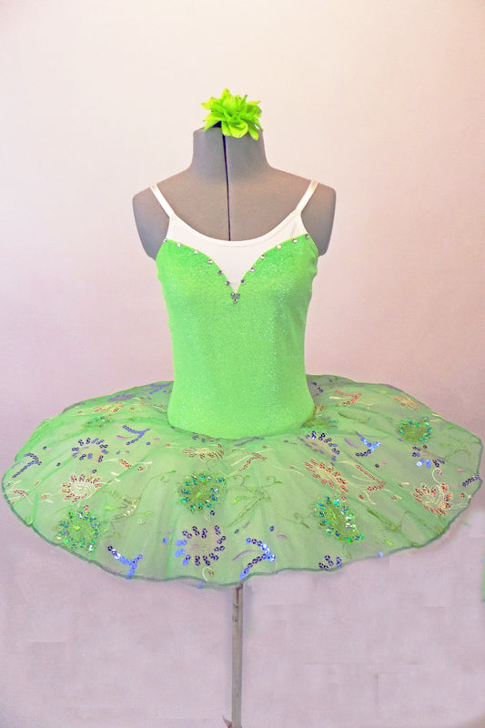 Delicate pale apple green tutu has a white pleated six-layer platter with the attached bodice and overlay. The sparkly green faux sweetheart cut is lined with crystals over a white camisole-style bodice. The sheer sequined lace overlay creates a really pretty soft look. Comes with a green floral hair accessory. Front