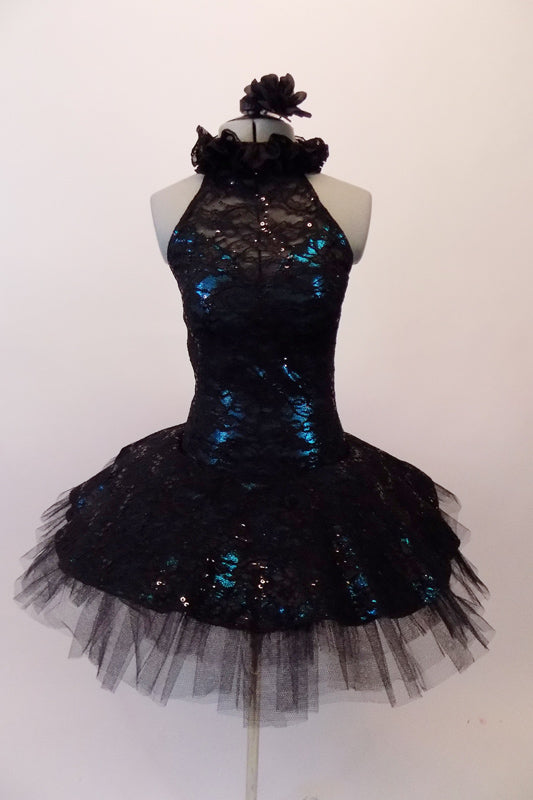 Stunning black sequined lace tutu has a ruffled halter collar neck with a shimmery teal underlay with sweetheart bust. The back has vertical angled straps for support. The bodice and overlay are attached to the six-layer black pleated tutu. Comes with a black floral hair accessory. Front