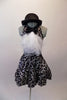 Black halter style dress has prominent silver swirled vine pattern. The neck has a large black bowtie from which cascades a large tulle layered ascot/bib. Comes with a black bowler hat. Front
