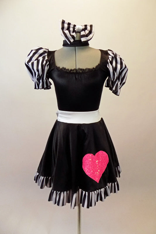 Sweet black dress has black and white striped pouffe sleeves and wide white waistband with large bow at back. The attached skirt has a black and white striped ruffle and a large pink sequined heart.  Comes with matching black and white striped hair bow. Front