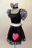 Sweet black dress has black and white striped pouffe sleeves and wide white waistband with large bow at back. The attached skirt has a black and white striped ruffle and a large pink sequined heart.  Comes with matching black and white striped hair bow. Side