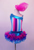 Costume has turquoise, crystal lined neckline with asymmetrical shoulder and straps with an adorable curly ruffled attached skirt in shades of blue pink and purple. The colours of the skirt compliment the striped vertical torso and the large pink hair accessory. Front