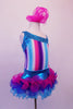 Costume has turquoise, crystal lined neckline with asymmetrical shoulder and straps with an adorable curly ruffled attached skirt in shades of blue pink and purple. The colours of the skirt compliment the striped vertical torso and the large pink hair accessory. Right side