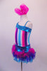 Costume has turquoise, crystal lined neckline with asymmetrical shoulder and straps with an adorable curly ruffled attached skirt in shades of blue pink and purple. The colours of the skirt compliment the striped vertical torso and the large pink hair accessory. Left side