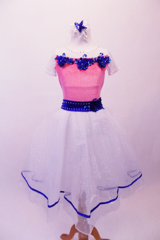 Romantic style ballet dress has pink glitter bodice with white crystal lined bust and cap sleeves. The bust and waist are embossed with royal blue 3-D sequined floral applique and large back bow. The attached white skirt is crystal-tulle with petticoat and trimmed with royal blue ribbon. Comes with a hair accessory. Front