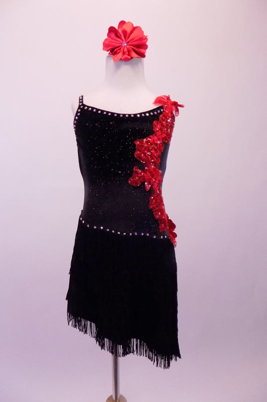 Black sequined dress is lined with crystals along the neckline and straps. The angled skirt is comprised of layers of black fringe lined at the hip by crystals. The left side of the torso from shoulder to hip is covered with a cascade of red 3-D floral sequined appliques. Comes with a red floral hair accessory. Front