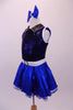 Blue-black costume has a diamond sequin bust with white trim open back and black leatherette crystalled collar. The attached blue skirt with crystal scattered organza overlay has a white belt with crystal buckle. Side