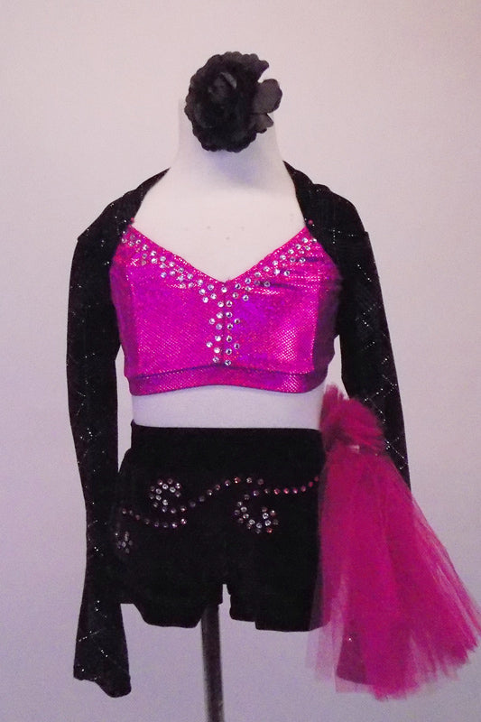 Sassy 3-piece costume has a bright pink, crystal lined half top that sits beneath a black velvet shrug with silver glitter tartan pattern. Comes with a floral hair accessory. Front