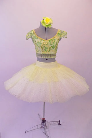 Professional pleated & hand tacked, 9-layer pancake tutu is two-piece. The tutu has an ivory basque & gold crystal tulle overlay with sequin accents & appliqued flowers. The bodice is a crop style top with pearl beaded fringe, gold & green sequined, applique floral lace & scalloped cap sleeves. Comes with hair flower. Front