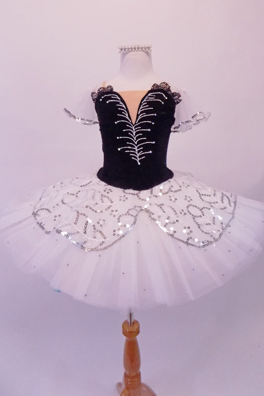 Pleated, hand tacked pancake tutu is a beautiful contrast of black & white. The tutu is scattered with crystals & has a silver sequined overlay. The black velvet bodice has a deep sweetheart cut with nude mesh centre & hand painted silver branch design. Comes with white tulle armbands and crystal hair barrette. Front