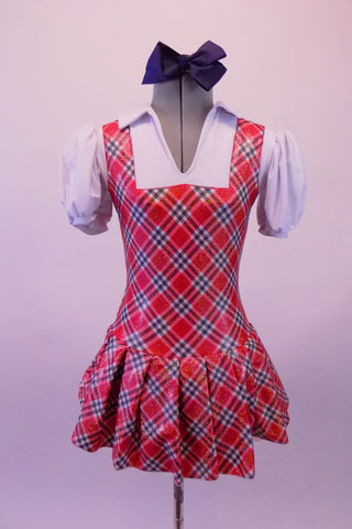 Red white and navy tartan school girl pinafore style costume has an attached pleated skirt and faux white blouse with pouffe sleeves and attached panty. Comes with large navy hair bow. Front