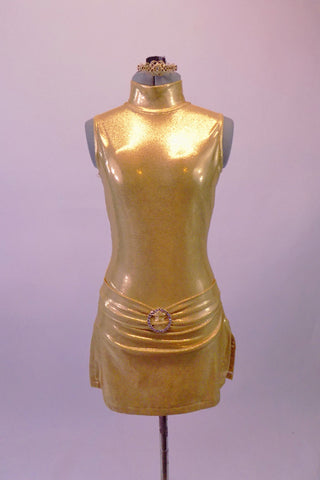 Gold leotard is simple yet stunning. It has a high collar and large open keyhole back. The attached skort-style skirt has side slits and a front gathered waist with crystal buckle accent. Comes with golden hair barrette. Front