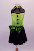 Back and lime green sequined costume has faux sweetheart bust with a black mesh upper and a green and black polka dot collar that matches the waistband and large bow accent. The back is open with corset style straps that hold the torso together. The attached black skirt completes the look. Comes with polka dot gauntlet and hair accessory. Front
