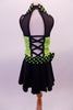 Back and lime green sequined costume has faux sweetheart bust with a black mesh upper and a green and black polka dot collar that matches the waistband and large bow accent. The back is open with corset style straps that hold the torso together. The attached black skirt completes the look. Comes with polka dot gauntlet and hair accessory. Back