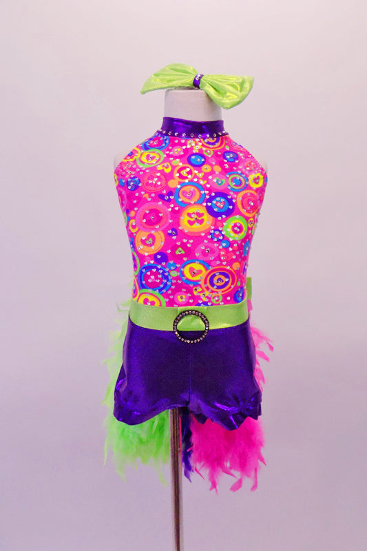 Halter style short unitard has a bright bubble-gum pink top with purple collar and brightly coloured heart-swirl patterns that is scattered with crystals. The attached purple short bottom has a lime green waistband with crystal buckle. The back has a tri-coloured boa feather tail that extends from a large bow at back. Comes with matching gauntlet and hair bow. Front