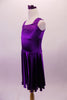 Stretch satin tank style purple dress has a wide shoulder strap. The bodice has a series of colour matched crystals in a large triangular shape and along the straps. Comes with matching floral hair accessory. Side