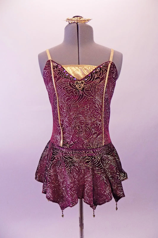 Merlot coloured leotard dress is velvet with gold swirl designs design, gold center inlay faux boning as well as a gold heart jewel at the bust. The short skirt has slight peaks with gold bead dangle accents. Comes with gold hair barrette. Front