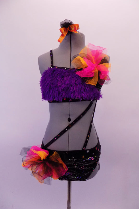 2-piece costume is attached by two crystal covered straps that extend from below the left bust across the front of the torso. The costume is a black base with colourful holographic dotted pattern. The brief has crystalled waistband & an orange-pink tulle accent at hip & the bust of the purple fur covered strappy bra. Front