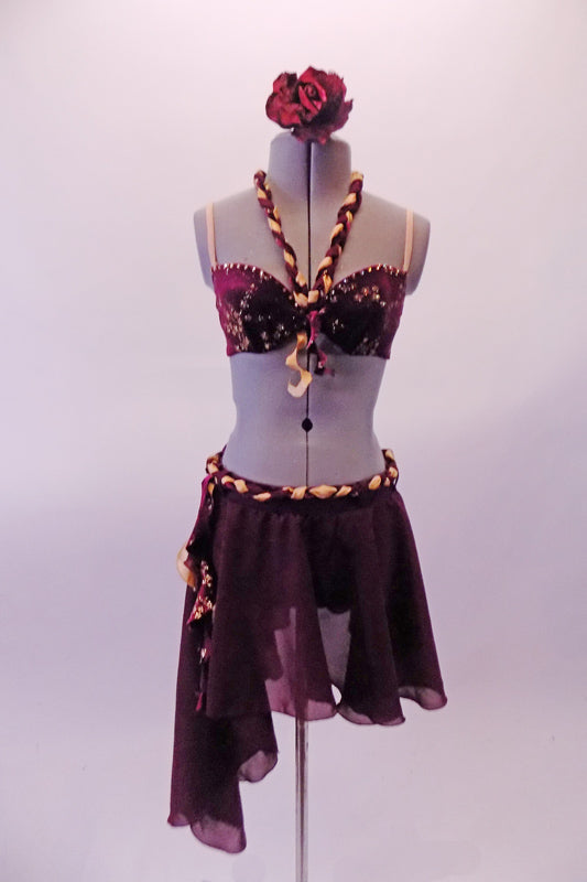 Deep burgundy two-piece costume has floral lace appliqued bra lined with crystals & nude straps. There is a gold & burgundy braided halter strap that attaches at the centre of the bust with small curly ruffle. The skirt with attached brief cascades long on the left side & has a matching braided belt & ruffle accent. Front