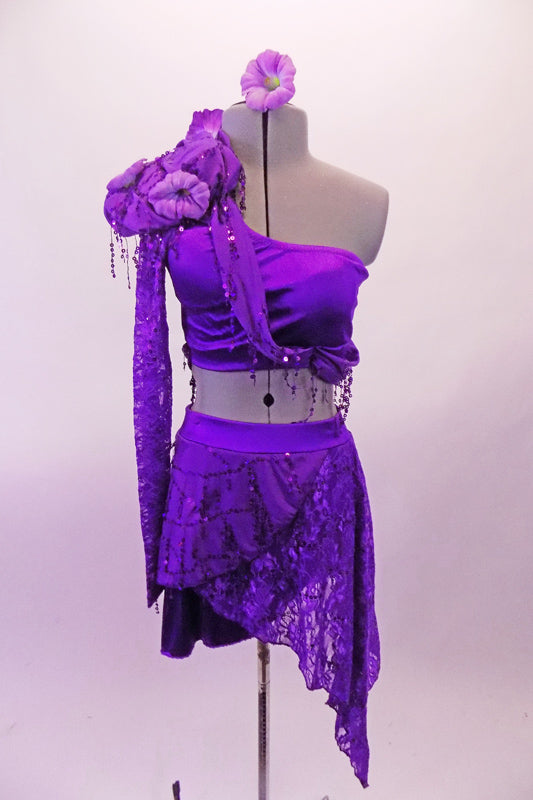 2-piece purple costume has a single shoulder half top with long lace sleeve. The right shoulder has an epaulette with purple morning glory flowers & dangling sequins. A purple sequined scarf drapes from right shoulder to below the left bust. Double-sided short-long lace sarong style skirt wraps around the hips. Front