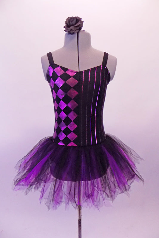 Black and purple-pink camisole leotard dress has a diamond pattern on the right side and pin-stripes on the left. The black and purple tulle attached skirt softens the abstract look. Comes with a black floral hair accessory. Front