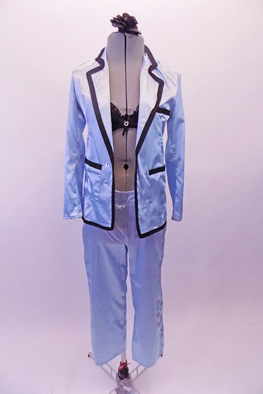 Ice blue satin pyjama style costume has pull-on pants a button front shirt/jacket top with black satin trim, pockets and lapels. There is a black lacey, ruffled bra (30A) that sit beneath the top with the buttons worn open. Comes with a floral hair accessory. Front