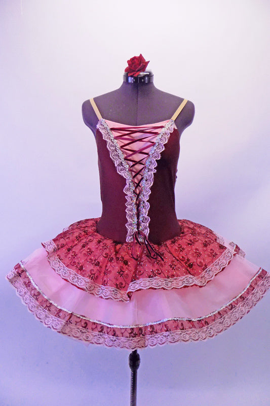 Sweet burgundy lycra bodice with corset lacing lace edged front has attached layered tutu skirt. The overlay is layers of pale pink and deep pink brocade edged with lace Comes with nude adjustable straps and floral hair accessory. Front