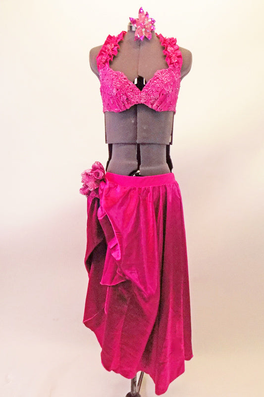 2-piece fuchsia costume has an underwire, halter style bra. The bra has embroidered lace & crystal covered cups with ruffled neck straps and triple crystal covered back straps. The sateen skirt with attached brief opens & gathers up the right side, with a lace floral accent. Comes with sequined hair accessory. Front